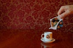 Füllende Kaffeetasse mit einer ungewöhnlichen Kaffeekanne. Stockfotografie