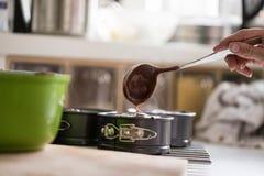 Füllendes Backenzinn der Frau mit Schokoladenkuchenmischung Stockbild