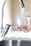Füllendes Glas Wasser in der Hand vom Küchenhahn Stockfotos