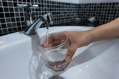 Füllendes Glas Wasser vom Edelstahlhahn Stockfoto