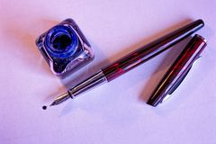 Füllfederhalter, blaue Tinte und Tintenfaß auf Weißbuchblatt stockfoto