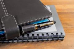 Füllfederhalter und Notizbuch auf Tabelle Lizenzfreie Stockbilder