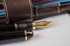 Füllfederhalter und Notizbuch auf Tabelle Lizenzfreie Stockfotos