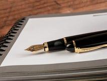 Füllfederhalter und Notizbuch auf Tabelle Lizenzfreies Stockfoto