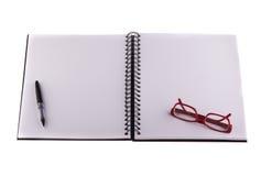 Füllfederhalter und rote Gläser gesetzt auf Notizbuch Stockfoto