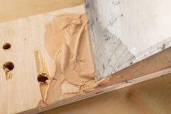 Füllmasse für ausbesserndes Holz Schalttafeln mit einem Planierenmittel lizenzfreies stockfoto
