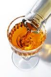 Füllung eines Weinglases durch ein alkoholisches Getränk Stockfoto