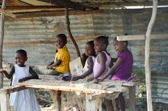 Fünf afrikanische Knaben, die in einem Stall lächeln stockfoto