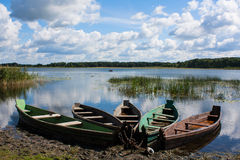 Fünf alte hölzerne Boote auf dem Seeufer Lizenzfreies Stockfoto