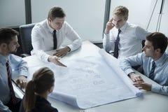 Fünf Architekten, die über einem Plan im Büro sich besprechen und planen Stockfotografie