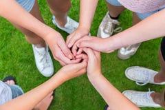 Fünf Arme mit den Händen von den Kindern verwickelt Lizenzfreie Stockbilder