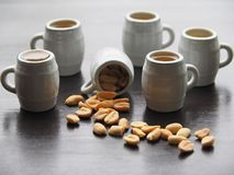 Fünf Bierkrüge und ein Becher mit gesalzenen Erdnüssen lizenzfreie stockbilder