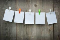 Fünf Blätter Papier auf Clothespins stockfotos