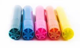 Fünf bunte Stifte auf einem weißen Hintergrund - gelb, rosa, orange, grün und blau Stockfoto