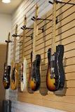 Fünf E-Gitarren, die am Präsentationsständer im Speicher für Verkauf hängen Stockbilder