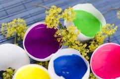 Fünf Eierschalen füllten mit Farben für Ostern-Dekoration Stockfotos