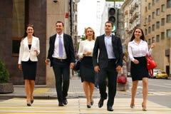 Fünf erfolgreiche Geschäftsleute, welche die Straße in der Stadt kreuzen Stockfoto