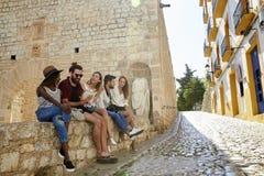 Fünf Freunde am Feiertag, der auf einer Wand in Ibiza sitzt Lizenzfreie Stockfotos