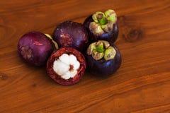 Fünf frische Mangostanfrüchte auf hölzerner brauner Tabelle Stockfotografie
