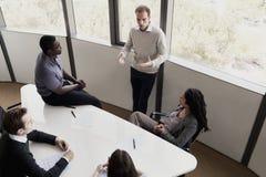 Fünf Geschäftsleute, die an einem Konferenztische sitzen und während eines Geschäftstreffens sich besprechen Lizenzfreies Stockbild