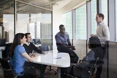 Fünf Geschäftsleute, die an einem Konferenztische sitzen und während eines Geschäftstreffens sich besprechen Stockfoto