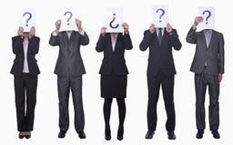 Fünf Geschäftsleute, die Papier mit Fragezeichen, undeutlich gemachtes Gesicht, Atelieraufnahme halten Lizenzfreie Stockfotos