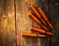 Fünf Gewehrpatronen auf Holzoberfläche Stockbilder