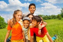 Fünf glückliche Kinder, die zusammen draußen streicheln Stockbild