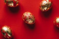 Fünf goldenes gefärbt und verziert mit Scheine Ostereiern auf rotem Hintergrund stockfoto