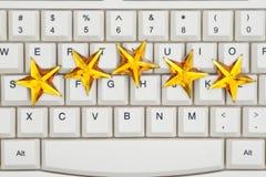 Fünf Goldsterne auf einer Tastatur lizenzfreie stockfotografie