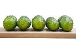 Fünf Gurken, die auf Ausschnittvorstand legen Stockfotos