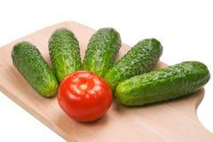 Fünf Gurken und eine Tomate auf Ausschnittvorstand Lizenzfreies Stockbild