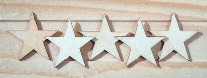 Fünf hölzerne Sterne auf einem hölzernen Hintergrund stockbild
