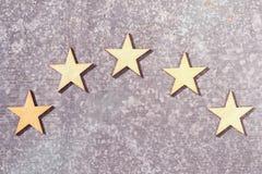 Fünf hölzerne Sterne auf einem Weißblechhintergrund stockfoto