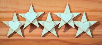 Fünf hölzerne Sterne und Herzen auf einem hölzernen Hintergrund stockbilder