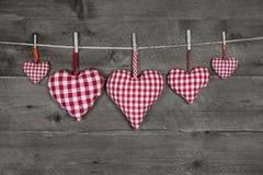 Fünf handgemachte rote karierte Herzen auf hölzernem grauem Hintergrund Lizenzfreie Stockfotografie