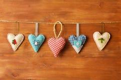 Fünf Herzen gemacht vom Stoff auf hölzernem Hintergrund Stockbild