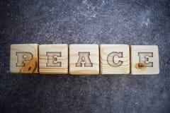 Fünf Holzklötze mit Wort - Frieden - auf grauem Hintergrund Lizenzfreie Stockfotografie