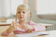 Fünf Jahre alte blonde Mädchen, die am Klassenzimmer und am Schreiben sitzen Lizenzfreies Stockfoto