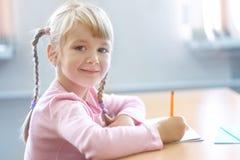 Fünf Jahre alte blonde Mädchen, die am Klassenzimmer und am Schreiben sitzen Stockfotografie