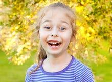 Fünf Jahre alte kaukasische Kindermädchen, die im Garten lachen Stockfoto
