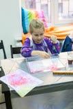 Fünf Jahre alte Mädchen, die Zeichnung auf dem Wasser machen Ebru-Kunst mit Ölfarben durch Wasseroberfläche Stockfotografie