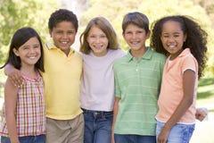 Fünf junge Freunde, die draußen lächelnd stehen Lizenzfreie Stockfotos