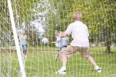 Fünf junge Freunde, die Fußball spielen Lizenzfreie Stockbilder