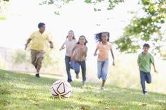 Fünf junge Freunde, die Fußball spielen stockfotografie