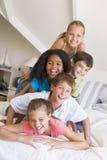 Fünf junge Freunde, die oben auf einander liegen lizenzfreies stockfoto