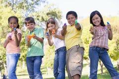 Fünf junge Freunde mit Wassergewehren draußen Stockbilder