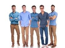 Fünf junge zufällige Männer, die zusammen bei der Arbeit stehen Stockfotos