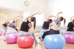 Fünf kaukasische weibliche Athleten, die Übungen mit Fitballs zuhause ausdehnen haben lizenzfreie stockfotografie