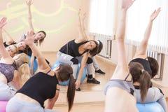 Fünf kaukasische weibliche Athleten, die das Ausdehnen von Übungen haben stockbild